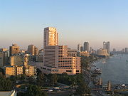 High-rises, including a multi-story white building in the foreground, dominate a sunset view of Cairo alongside the Nile, which is shown flowing under a bridge carrying a busy street
